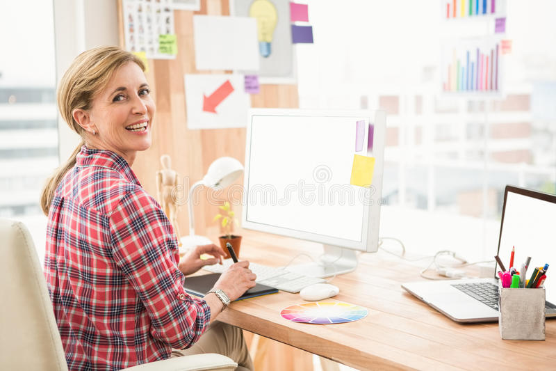 Glimlachende toevallige ontwerper die met becijferaar werken royalty-vrije stock fotografie