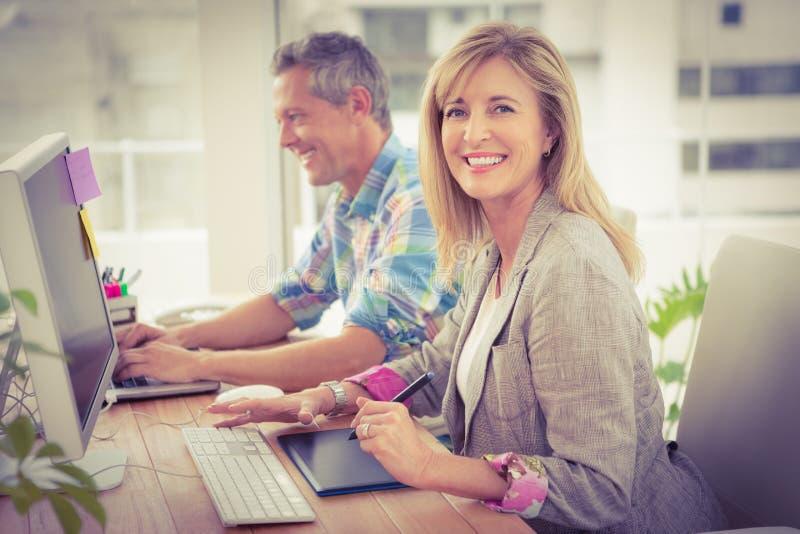 Glimlachende toevallige ontwerper voor haar werkende collega royalty-vrije stock fotografie