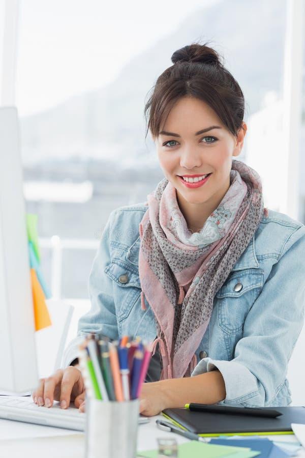 Glimlachende toevallige vrouw die computer in bureau met behulp van stock foto