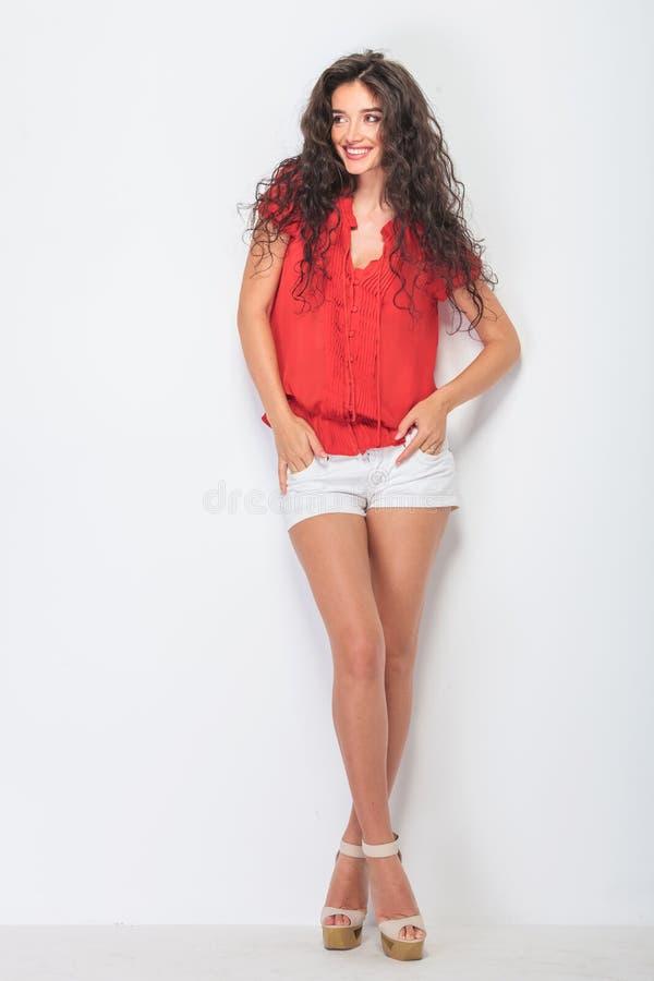 Glimlachende toevallige vrouw die zich met haar gekruiste benen bevinden stock afbeelding