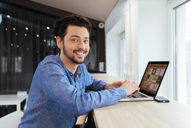 Glimlachende toevallige zakenman die laptop computer met behulp van stock fotografie