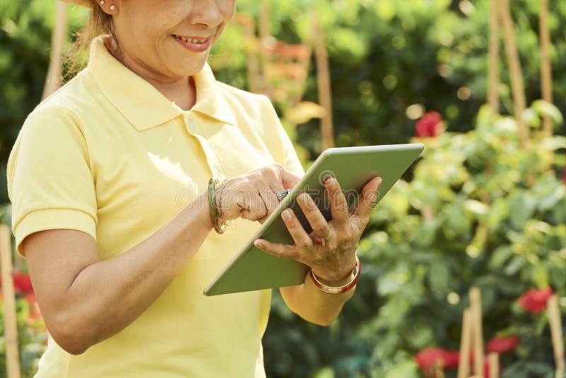 Glimlachende tuinman met tabltcomputer stock afbeeldingen