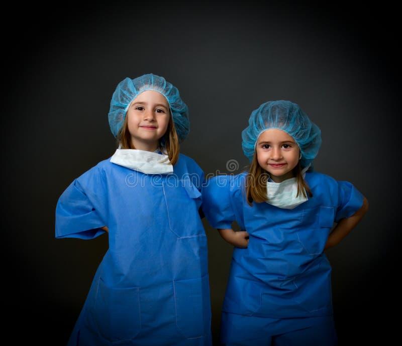 Glimlachende tweelingkinderen artsen stock afbeeldingen