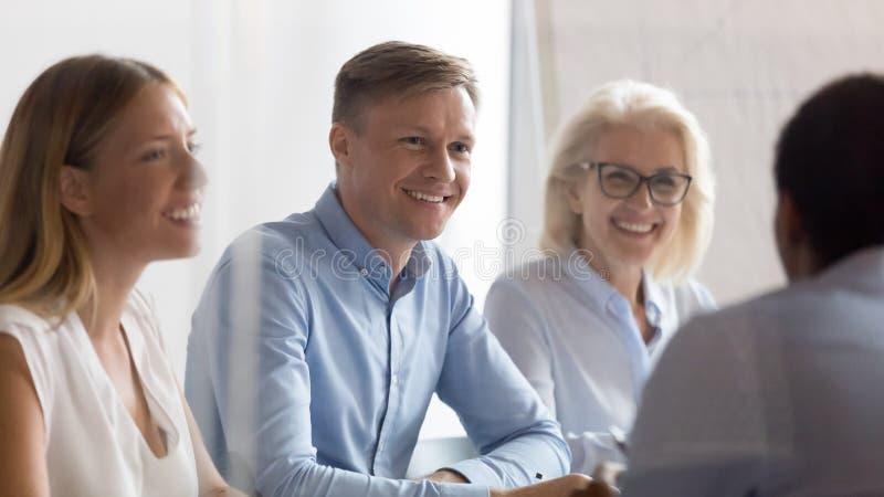 Glimlachende u-groep die het kandidaat spreken bij baangesprek bekijken stock foto