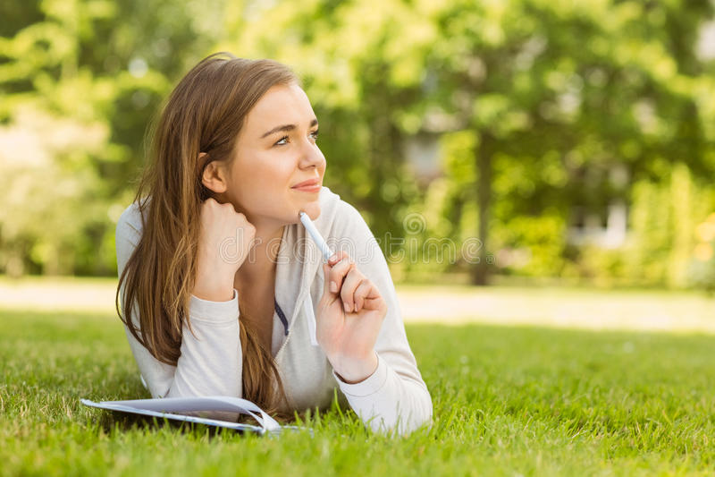 Glimlachende universitaire student die en het denken liggen stock afbeeldingen