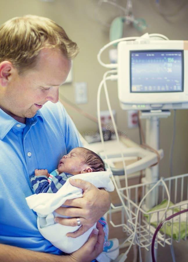 Glimlachende vader die zijn pasgeboren babyzoon in een het ziekenhuisruimte houden royalty-vrije stock afbeeldingen