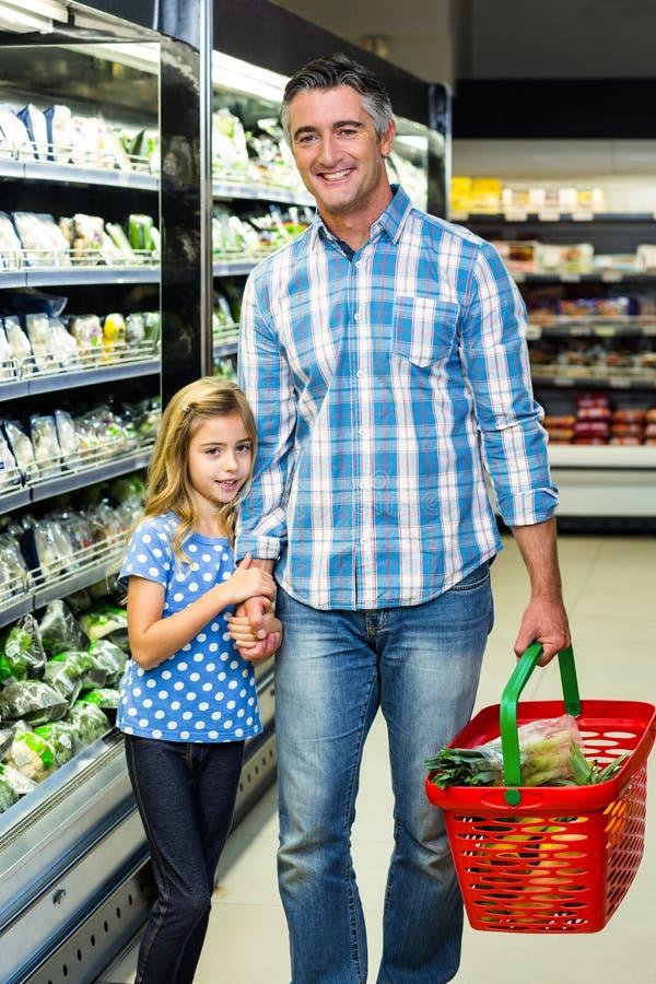 Glimlachende vader en dochter bij de supermarkt royalty-vrije stock foto