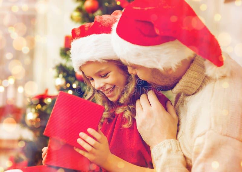 Glimlachende vader en dochter het openen giftdoos stock foto