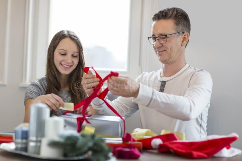 Glimlachende vader en dochter het verpakken thuis aanwezige Kerstmis stock foto