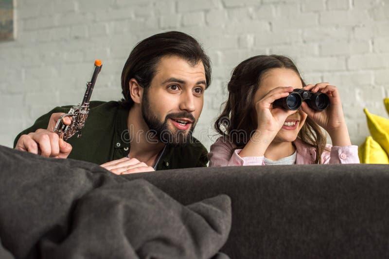 glimlachende vader en dochter met verrekijkers en stuk speelgoed kanon het verbergen achter bank en samen het spelen royalty-vrije stock foto