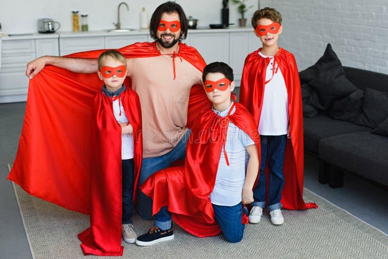 glimlachende vader en kleine zonen in rode superherokostuums royalty-vrije stock afbeeldingen