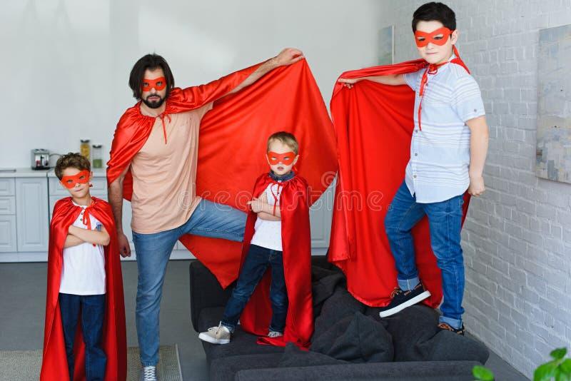 glimlachende vader en kleine zonen in rode superherokostuums royalty-vrije stock fotografie