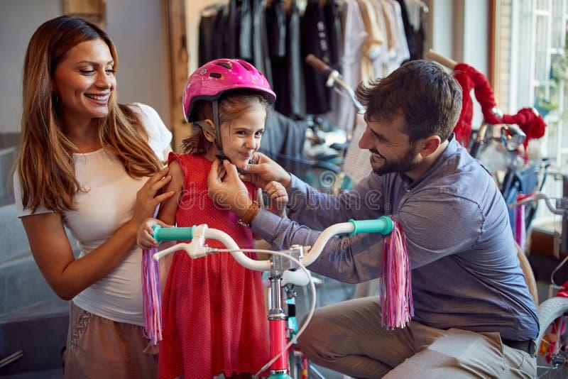 Glimlachende vader en moeder het winkelen winkelen de nieuwe fiets en de helmen voor meisje in fiets stock afbeelding