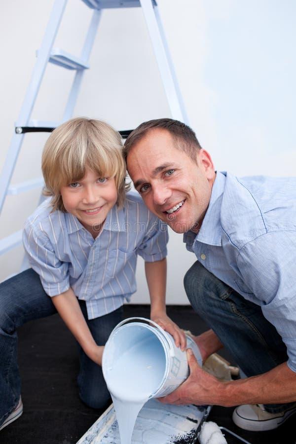 Glimlachende vader en zijn zoon die verf voorbereiden stock foto's