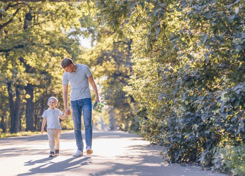 Glimlachende vader en zoon met een skateboard stock afbeeldingen