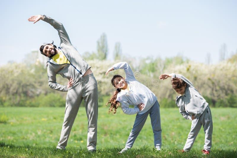 glimlachende vader met dochter en zoon die lichaamsbeweging op grasrijke weide doen royalty-vrije stock foto's