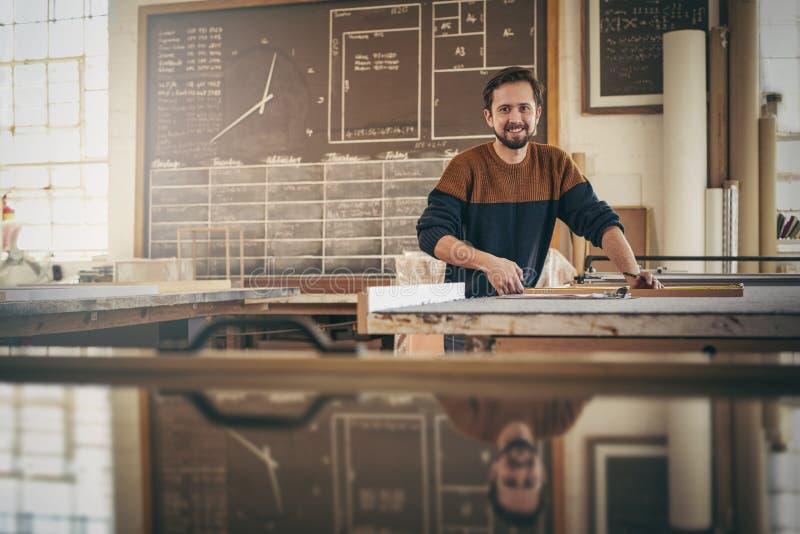 Glimlachende vakman aan het werk in zijn houtbewerkingsstudio stock afbeeldingen
