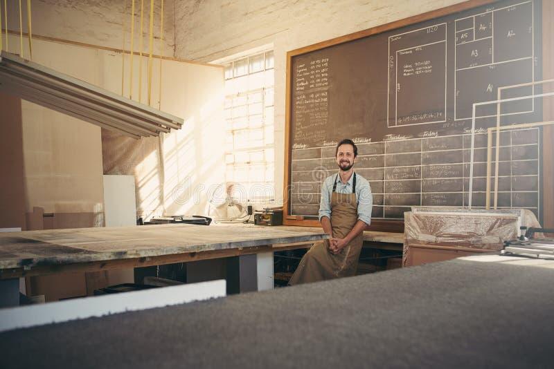 Glimlachende vakman die in zijn workshop de camera bekijken stock fotografie
