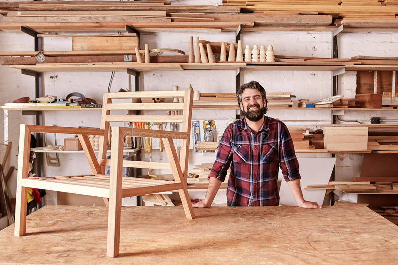 Glimlachende vakman in zijn houtbewerkingsstudio met houten stoelkader royalty-vrije stock foto