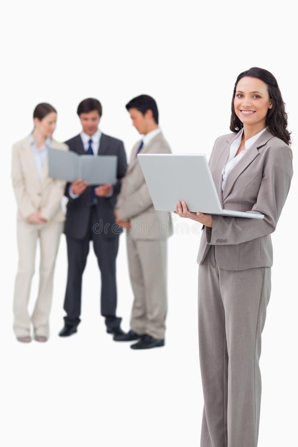 Glimlachende verkoopster met laptop en vennoten achter haar stock afbeeldingen