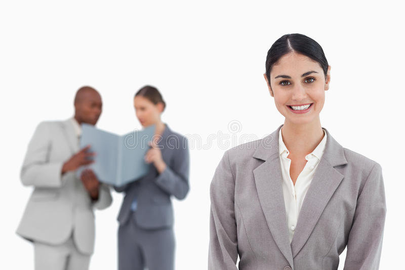 Glimlachende verkoopster met medewerkers achter haar stock fotografie
