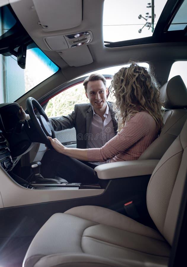 Glimlachende verkoper die aan vrouwelijke klantenzitting spreken in auto stock foto