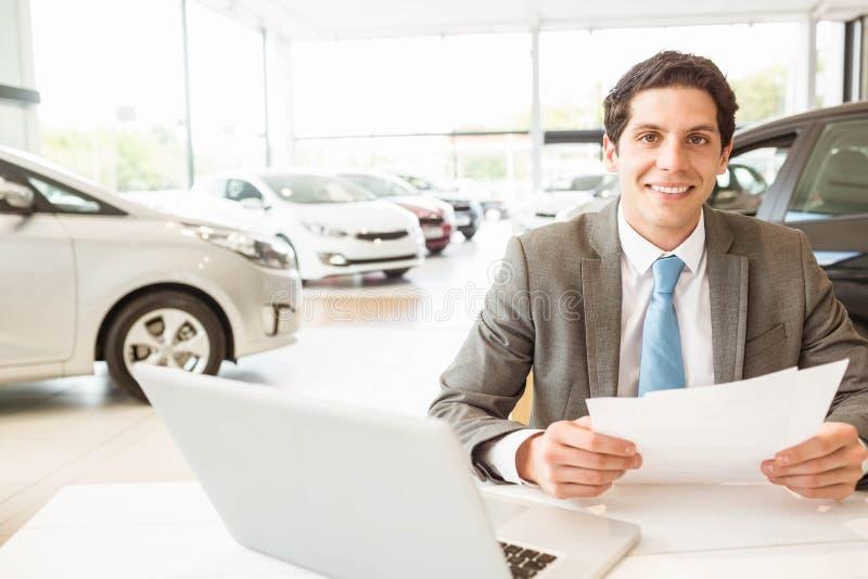 Glimlachende verkoper die een document lezen royalty-vrije stock afbeelding