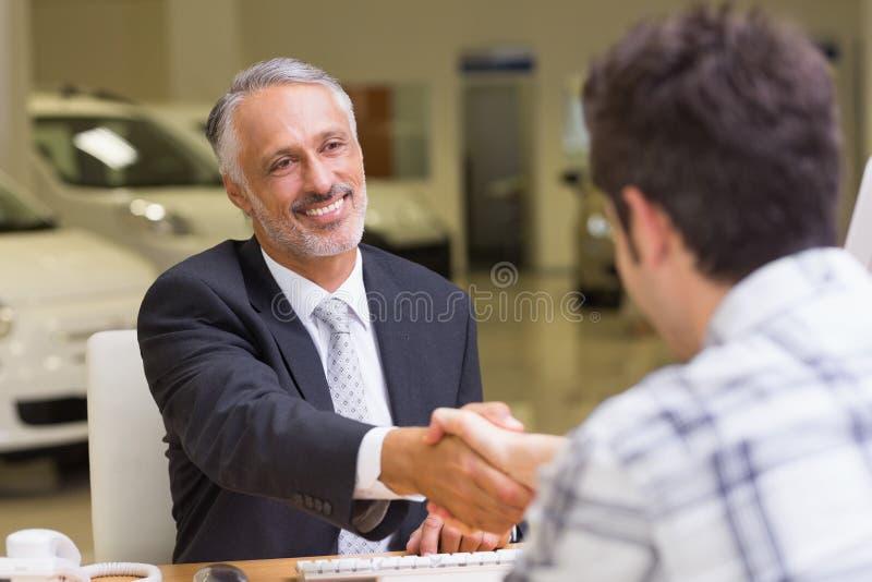 Glimlachende verkoper die een klantenhand schudden stock foto's