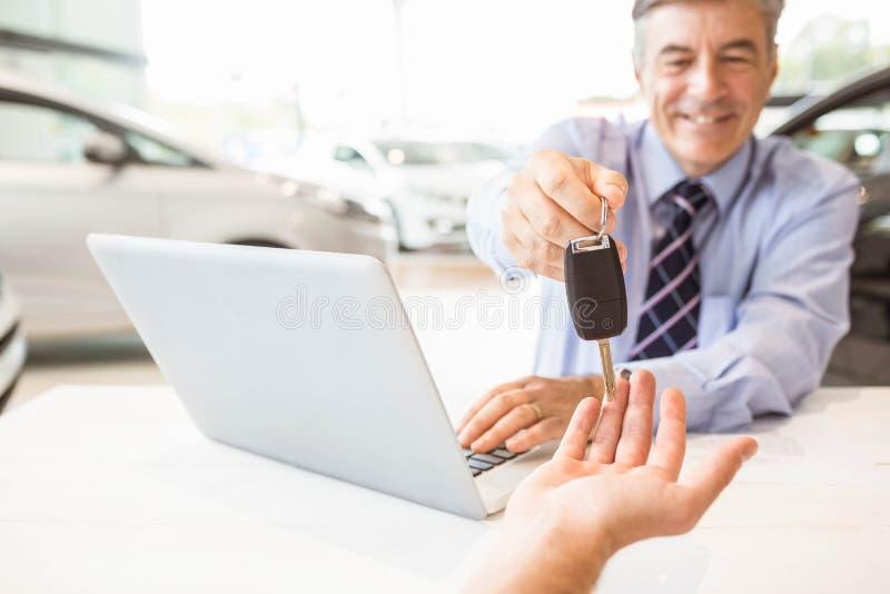 Glimlachende verkoper die een sleutel van de klantenauto houden stock foto