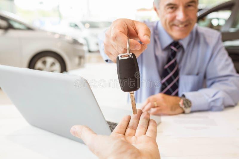 Glimlachende verkoper die een sleutel van de klantenauto houden stock afbeelding