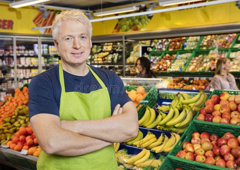 Glimlachende Verkoper Standing Arms Crossed door Vruchten in Opslag stock foto's