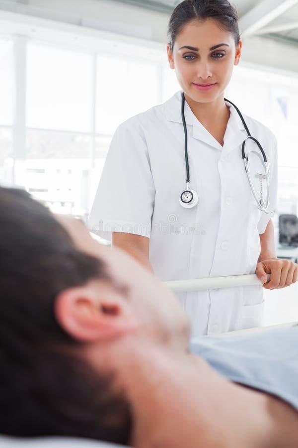 Glimlachende verpleegster die een patiënt behandelen royalty-vrije stock foto