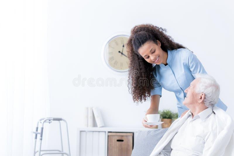 Glimlachende verpleegster die thee geven aan bejaarde in witte verzorgingshou stock foto