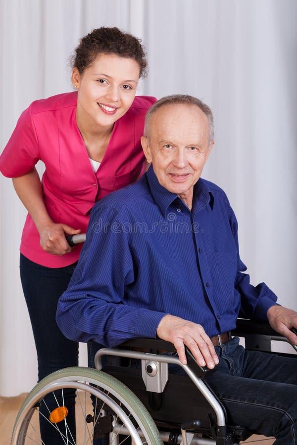 Glimlachende verpleegster die zich door de gehandicapten bevinden royalty-vrije stock foto