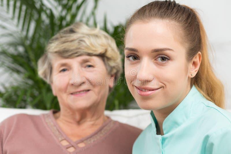 Glimlachende verpleegster met een bejaarde dame stock fotografie