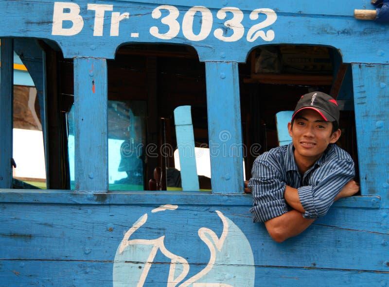 Glimlachende Vietnamese visser bij zijn houten boot royalty-vrije stock foto's