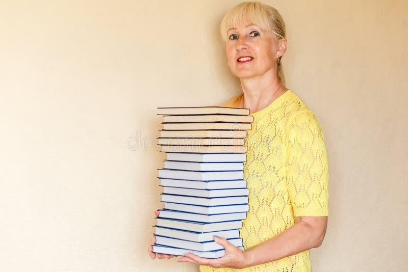 Glimlachende vijftig-jaar-oude vrouw in een geel jasje die een grote stapel identieke boeken houden stock afbeeldingen