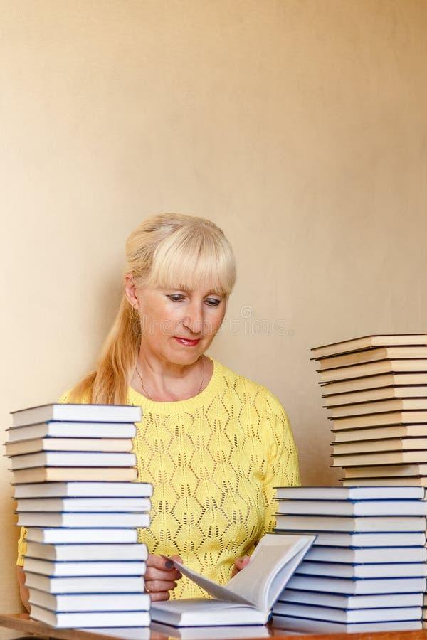 Glimlachende vijftig-jaar-oude vrouw in een gele sweater die een boek leest Huisbibliotheek royalty-vrije stock fotografie