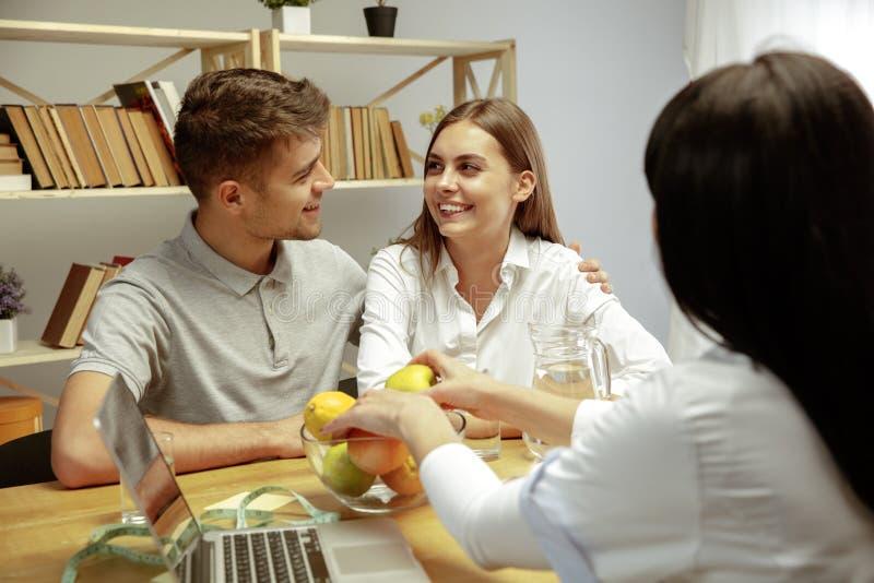 Glimlachende voedingsdeskundige die een gezonde voedingplan tonen aan patiënt royalty-vrije stock fotografie