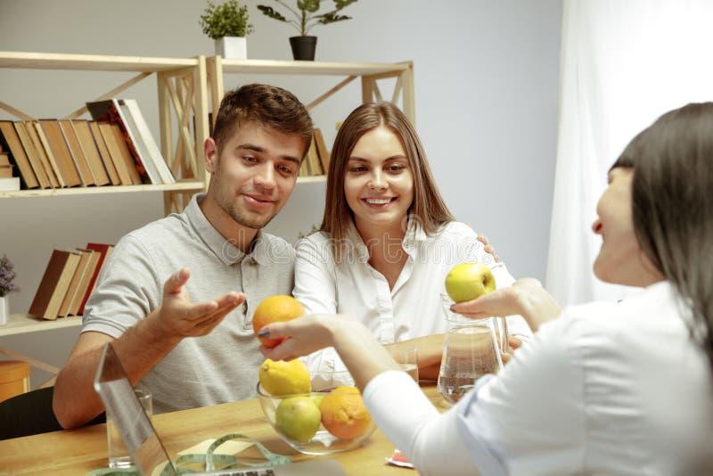 Glimlachende voedingsdeskundige die een gezonde voedingplan tonen aan patiënt royalty-vrije stock foto's