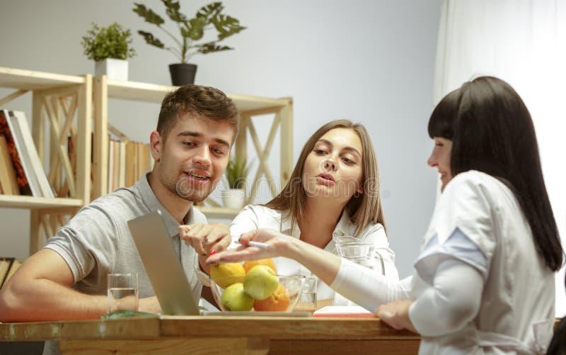 Glimlachende voedingsdeskundige die een gezonde voedingplan tonen aan patiënt royalty-vrije stock foto