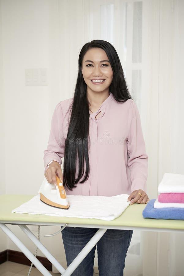 Glimlachende volwassen huisvrouw met ijzer thuis royalty-vrije stock afbeelding