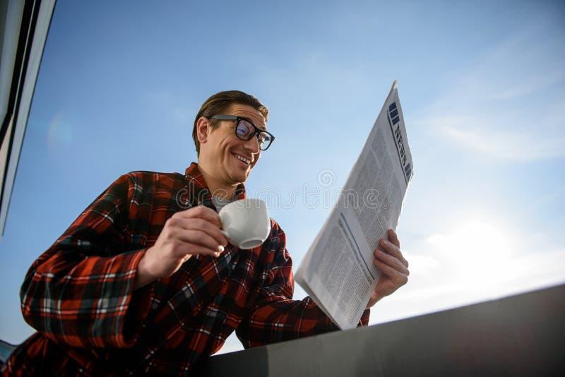 Glimlachende volwassen mens die met wonder in krant kijken stock foto's