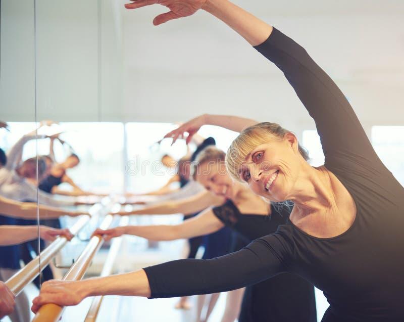 Glimlachende volwassen vrouwen die zich in balletklasse uitrekken royalty-vrije stock afbeeldingen