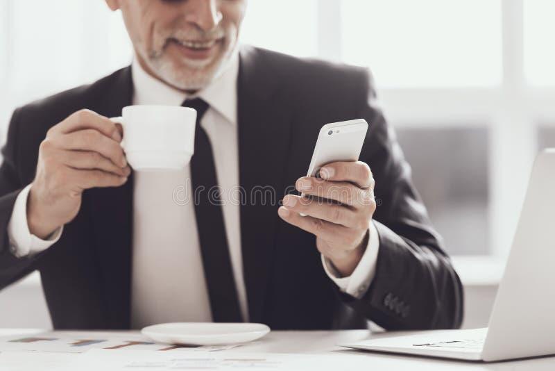 Glimlachende Volwassen Zakenman op Koffiepauze op het Werk stock foto