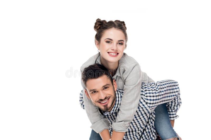 glimlachende vriend die op de rug aan meisje geven stock foto