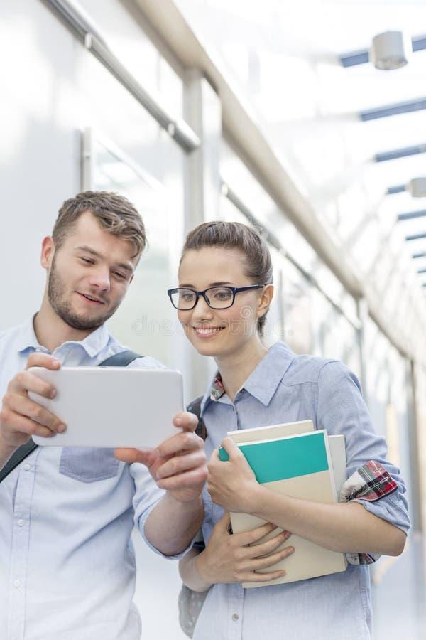 Glimlachende vrienden die digitale tablet in universitaire campus bekijken stock foto's