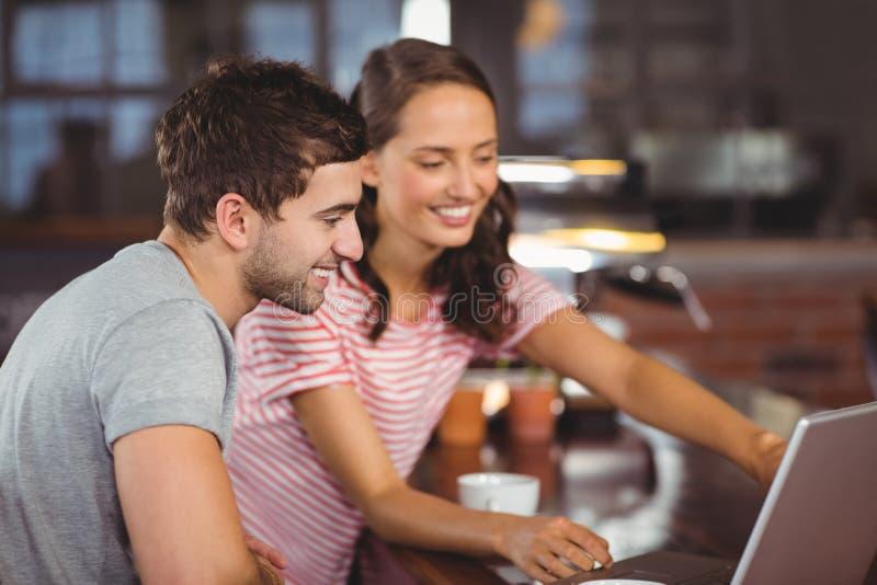 Glimlachende vrienden die en laptop het scherm richten bekijken stock afbeelding