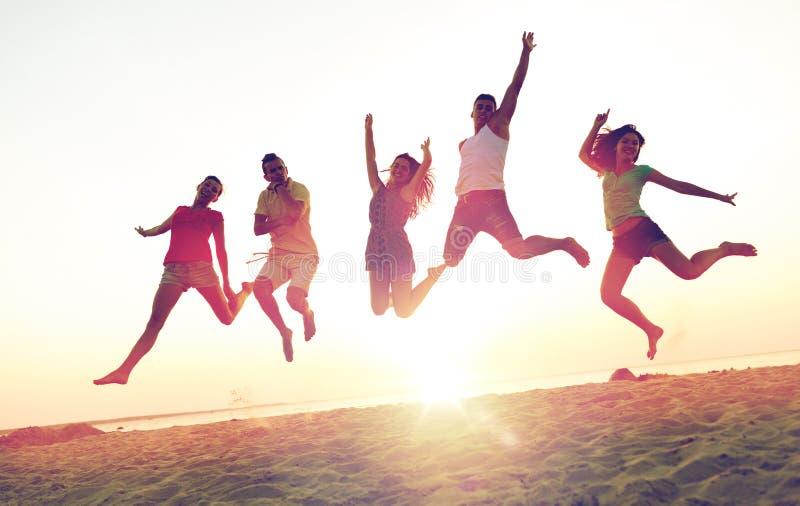 Glimlachende vrienden die en op strand dansen springen royalty-vrije stock afbeelding
