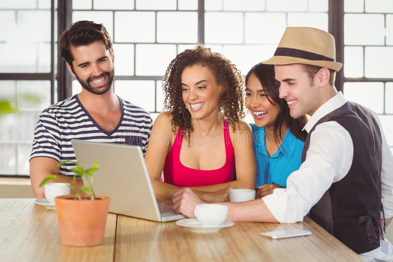 Glimlachende vrienden die laptop en het hebben van koffie bekijken royalty-vrije stock afbeeldingen